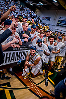16 March 2019: University of Vermont Catamount Forward Anthony Lamb, a Junior from Toronto, Ontario, kneels in from of coach John Becker and teammates, celebrating a victory against the UMBC Retrievers in the America East Championship Game at Patrick Gymnasium in Burlington, Vermont. The Catamounts defeated the Retrievers 66-49, avenging their loss against the same team in last years' Championship Game. Mandatory Credit: Ed Wolfstein Photo *** RAW (NEF) Image File Available ***