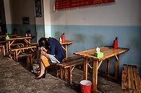 A woman from the country side falls asleep during work in a restaurant in the heart of a relocation housing estate in China's southwestern Chongqing city. She, like her clients, were recently relocated from nearby villages that were razed by the government to make way for urban high-rises. The Chinese government plans to move 250 million rural residents into urban areas over the coming dozen years though it is unclear whether people want to move and where the money for this project will come from. Further urbanisation is meant to drive up consumption to counterbalance an export orientated economy and end subsistence farming but the drive to get people off the land is causing tens of thousands of protests each year. /Felix Features
