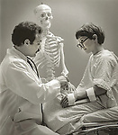 Vintage B&W. 83-145-A #31. Boy and doctor with arm splint and skeleton model. Scan from print
