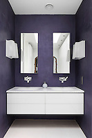 This purple-painted bathroom boasts a pair of contemporary wash basins above a wall-mounted drawer unit