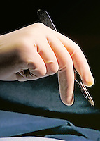 Gloved hand of a surgeon holding a scalpel.