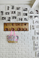 A collection of black and white family photographs are displayed on a white painted brick wall. A pink bag hangs from a wooden peg rail.