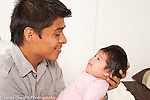 7 week old newborn baby girl held by father interaction responding to his talking