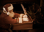 Santa Claus writing with a feather fountain pen in a book at a desk near a fireplace