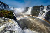Overlook on the impressive Iguazu Falls' multiple cataracts, with a beautiful rainbow across the river in Iguacu National Park, Iguazu Brazil