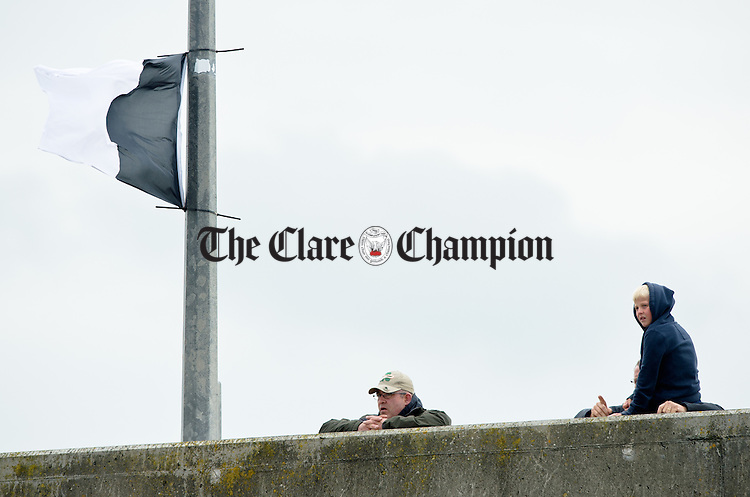 Spectators look on from the pier wall at the All-Ireland  Currach Regatta at Doonbeg. Photograph by John Kelly.