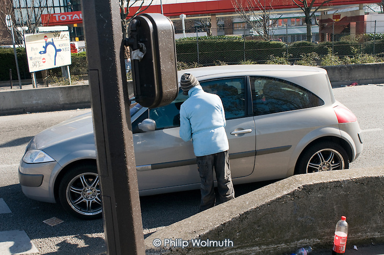 A young Roma boy begs from a car stopped at traffic lights in a street on the outskirts of Paris.