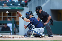 Toledo Mud Hens catcher Cameron Rupp (26) prepares to receive a pitch as home plate umpire Jeremy Riggs looks on during the game against the Charlotte Knights at BB&T BallPark on April 24, 2019 in Charlotte, North Carolina. The Knights defeated the Mud Hens 9-6. (Brian Westerholt/Four Seam Images)