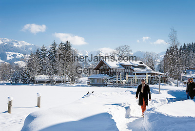 Austria, Tyrol, Reith near Kitzbuhel: winter walk around idyllic lake Schwarzsee on the outskirts of Kitzbuhel, at background Kitzbuhel Alps | Oesterreich, Tirol, Reith bei Kitzbuehel: Winterspaziergang am Schwarzsee, im Hintergrund die Kitzbueheler Alpen