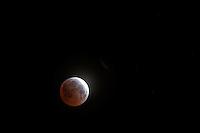 A lunar eclipse, in progress, nearing maximum on April 5, 2015.  Viewed from near San Francisco, California.
