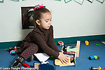 Education preschool 3-4 year olds girl talking to herself  as she plays with doll house dolls and toy beds