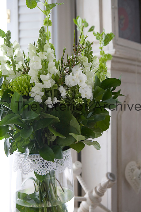Detail of a vase of white snapdragons and green chrysanthemums