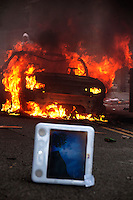 A computer on a road in front of a vehicle on fire on Ellingfort Road in Hackney. London saw the beginnings of riots on Saturday evening, after a peaceful protest in response to the shooting by police of Mark Duggan during an attempted arrest, escalated into violence. By the third night of violence, rioting had spread to many areas of the capital and to other cities around the country.
