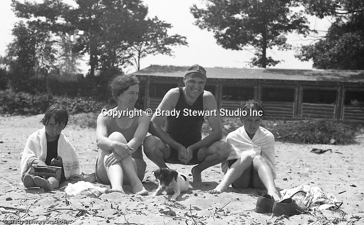 Markleysburg PA:  Stewart family camping and swimming at Youghiogheny Lake.  Brady Jr., Brady Sr., Sara and Sally Stewart relaxing on the beach with Pepe (their dog)>