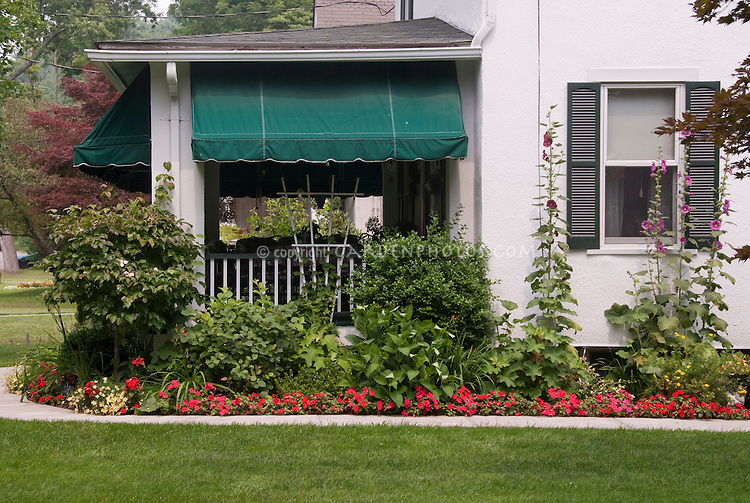 Summer garden next to house and front porch with hollyhocks Alcea, impatiens