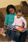 3 year old girl at home with mother reading book on couch