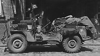 BNPS.co.uk (01202) 558833. <br /> Pic: Bosleys/BNPS<br /> <br /> Pictured: An SAS jeep parked by a Nazi flag. <br /> <br /> Never before seen photos taken by a fishmonger turned SAS hero behind enemy lines in World War Two have come to light 76 years on.<br /> <br /> Sergeant Samuel Rushworth, of the 2nd Special Air Service, was dropped into occupied France two days before D-Day in June 1944.<br /> <br /> They were tasked with disrupting German reinforcements dispatched to Normandy following the Allied landings.