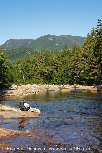 A hiker on the side of the East Branch of the Pemigewasset River in the Pemigewasset Wilderness in Lincoln, New Hampshire. This forest was logged during the East Branch & Lincoln Railroad era, which as was a logging railroad in operation from 1893-1948.