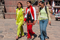 Bhaktapur, Nepal.  Women Walking through Taumadhi Tole Square Blend Traditional and Western Dress Styles.