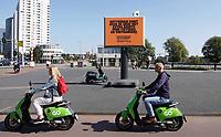 Nederland - Rotterdam - 2020.  Tekst op het bord: Rotterdam komt over de brug met extra ruimte voor fietsers en voetgangers. Elektrische deelscooters van Go Sharing.   Foto ANP / Hollandse Hoogte / Berlinda van Dam