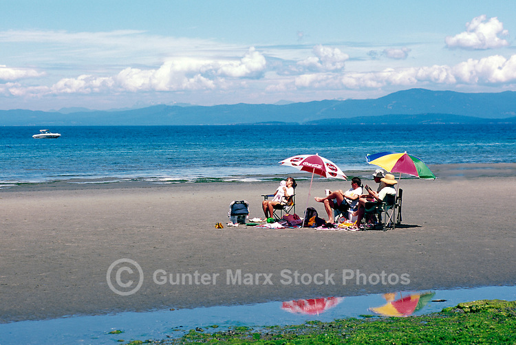 """A Family sunbathing on the Beach at Qualicum Beach, in the """"Oceanside Region"""" of Vancouver Island, British Columbia, Canada"""