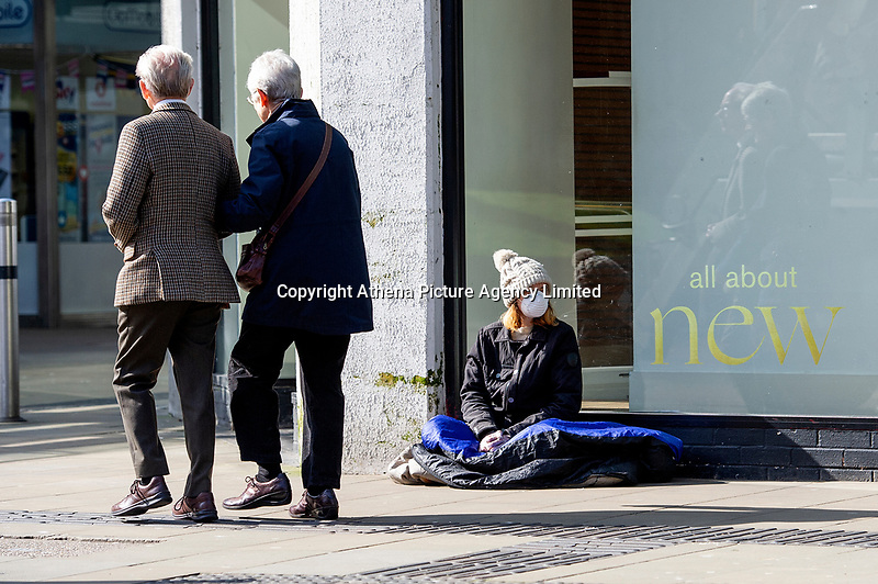 Pictured: A masked lady sits down in Swansea City Centre during the Covid-19 Coronavirus pandemic in Wales, UK, Swansea, Wales, UK. Monday 23 March 2020