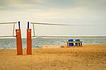 Madison Beach Club. Volleyball nets on beach with trash barrels.