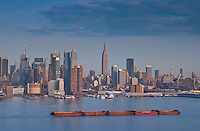 Long barge in Hudson river with Manhattan skyline and Empire State Building skyscrapers on background