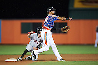 Aberdeen Ironbirds shortstop Ricardo Andujar (18) throws to first as Keach Ballard (32) slides in during a game against the Tri-City ValleyCats on August 6, 2015 at Ripken Stadium in Aberdeen, Maryland.  Tri-City defeated Aberdeen 5-0 in a combined no-hitter.  (Mike Janes/Four Seam Images)