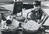 1973 FILE PHOTO -<br /> <br /> His mother doing business - cooking meals right on the sidewalk and he helping with dish washing.