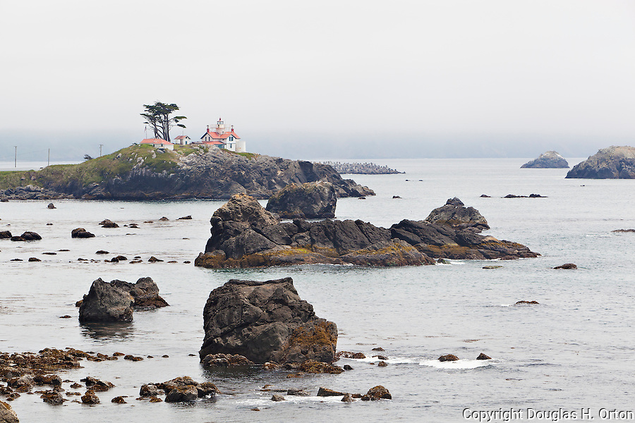 Battery Point Lighthouse, Crescent City California, near the Oregon and California border perches atop a rocky atol at the entrance to Crescent Bay on the Pacific Ocean Coast.  The lighthouse, reachable at low tide,.was lit in 1858.