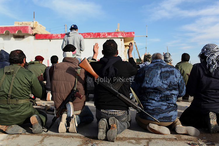 Opposition fighters pray at the Brega checkpoint, Libya, March, 12, 2011. The rebels continued to lose ground against loyalist forces of Col. Muammar Qaddafi and were attacked from the air, the sea and the ground.
