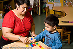 Educaton preschool 3-4 year olds female teacher working with boy on color recognition using colorful connecting blocks horizontal
