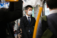 A masked businessman on the subway in Tokyo.