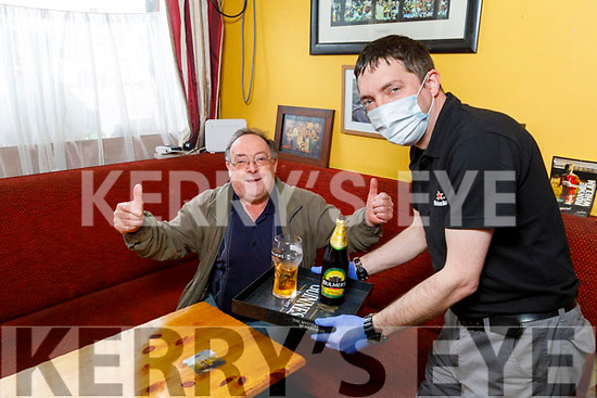 Mike Flynn enjoying his first pint as he receives table service from Stephen Bell in The Castle Inn in Castlemaine on Monday.