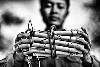 A Kachin Independence Army soldier holds landmines he made at a front-line army camp. Two weeks later he was killed when planting one.