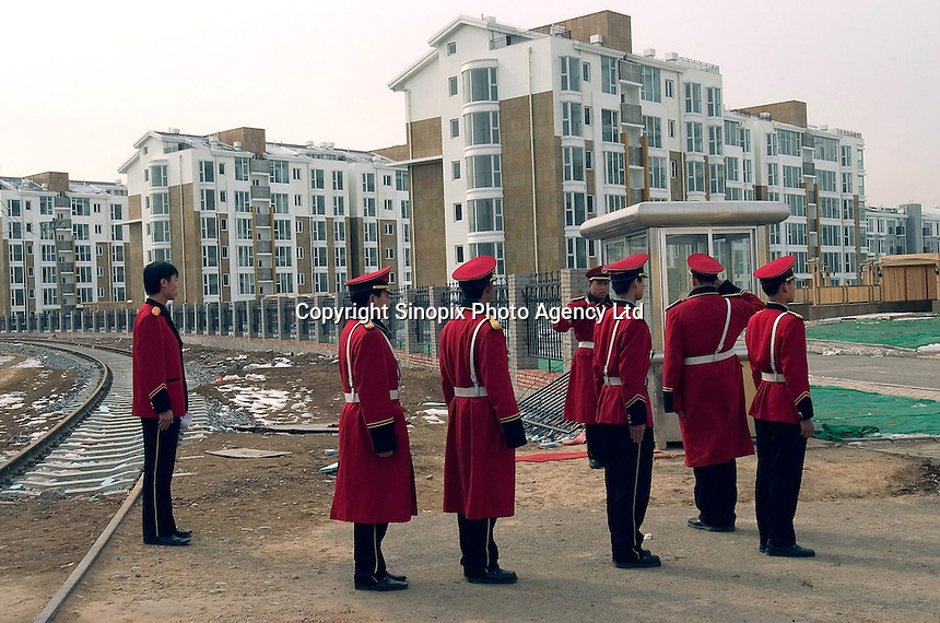 Security guards shift work while a group of workers pass by in a new luxury property in Beijing, China..23-FEB-05