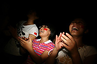 CHINA. Beijing. Members of the Chinese public clapping and cheering whilst watching the opening ceremony of the Beijing Summer Olympics. 2008