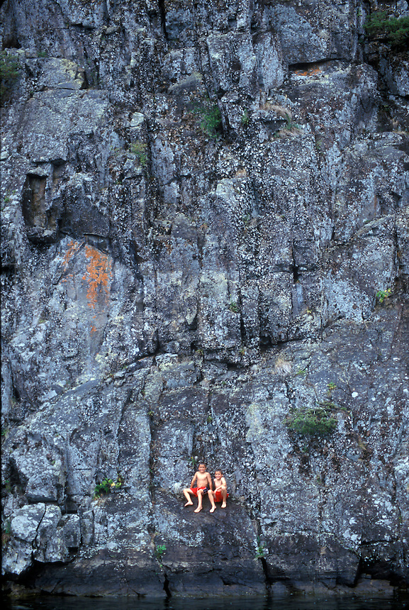 Twin boys dive and swim off rock wall in Lake George, New York