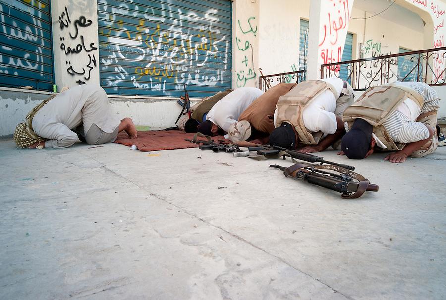 Anti-Gaddafi fighters pray near the front line in Sirte, Libya.