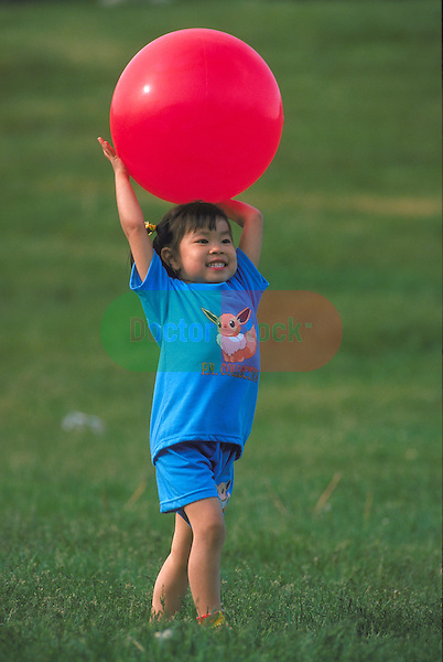 young girl holding ball over head in park