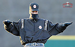 Umpire Mark Fitzgerald signals safe in a pickoff attempt during a cold-weather game between the University of South Carolina Upstate Spartans and the UNC Asheville Bulldogs on Tuesday, March, 25, 2014, at Cleveland S. Harley Park in Spartanburg, South Carolina. (Tom Priddy/Four Seam Images)