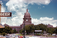 """Vintage view of the Texas State Capitol with """"Beer"""" sign at the Capitol Tavern, favorite bar of the Texas Senate and Texas House of Representatives for drinking and negotiating legislation. Line of retro cars and trucks parked along the Capitol in July 1958 - Stock Image."""