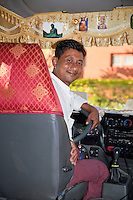 Myanmar, Burma.  Driver of Tourist Van, Buddha Protective Talismans on Windshield Curtain.