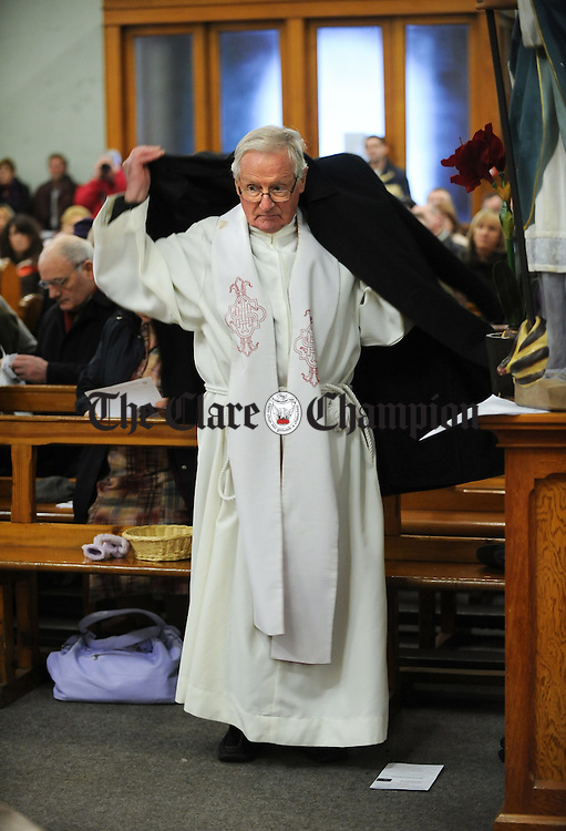 Cannon Caimin O Carroll dons his overcoat as temperatures drop during the final mass as part of  the Ceremony of Transition in Our Lady's church, Ennis. Photograph by John Kelly.