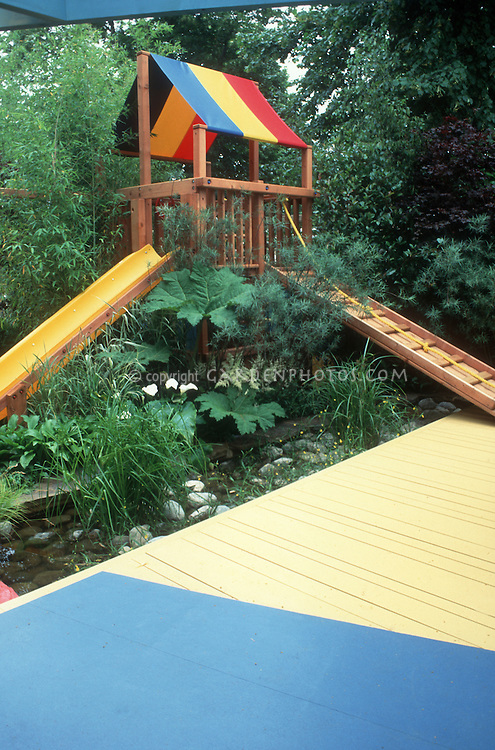 Child's backyard tree house, with slide, ramp, colorful blue and yellow deck