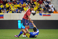 Juan Agudelo (18) of the United States helps up Eduardo Morante (2) of Ecuador. The men's national team of the United States (USA) was defeated by Ecuador (ECU) 1-0 during an international friendly at Red Bull Arena in Harrison, NJ, on October 11, 2011.