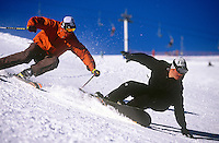 A snowboarder and a skier in action