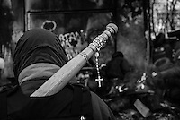 A rosary is laced to a makeshift mace by a protester.  Orthodox  symbols   became an iconic presence in the forefront of the protest