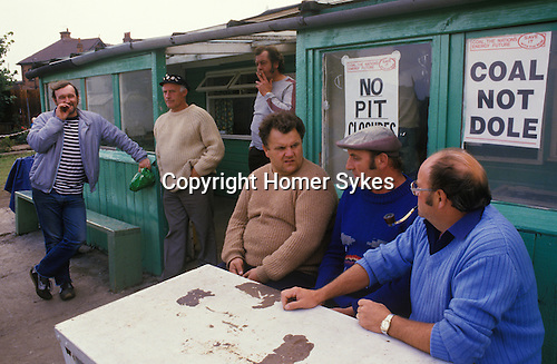 """Shirebrook, Derbyshire.1984  <br /> At Shirebrook Colliery striking miners pass the time of day at their local strike office. Miner's wives came together to give support to their men, and provide food parcels for those miners in need.  Notices in their windows proclaim 'Coal the Nations Energy Future. Save it with the NUM. Coal Not Dole."""""""